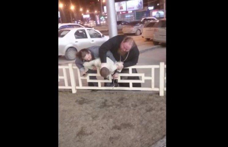 Як на Росії батюшка в рясі посеред міста побив людину хрестом