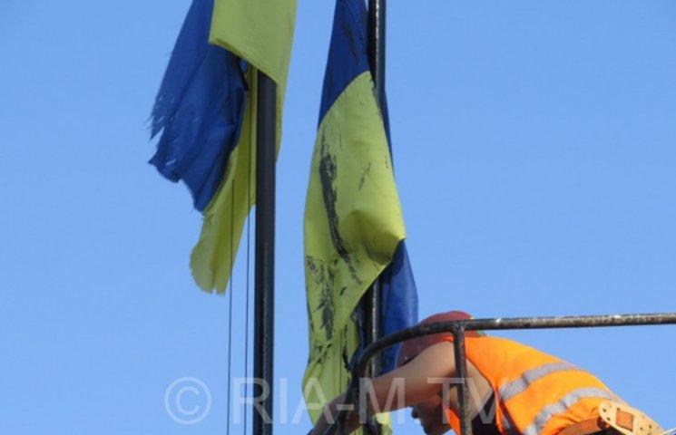 """У Мелітополі комунальники """"пофарбували"""" прапори України в чорний колір"""