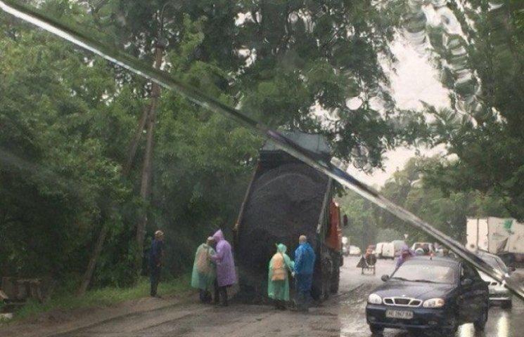 У Дніпропетровську дорогу ремонтують під дощем, а городяни скидаються на асфальт для ям (ФОТО)